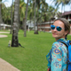 beautiful girl with blue backpack on a path with palm trees - PhotoDune Item for Sale
