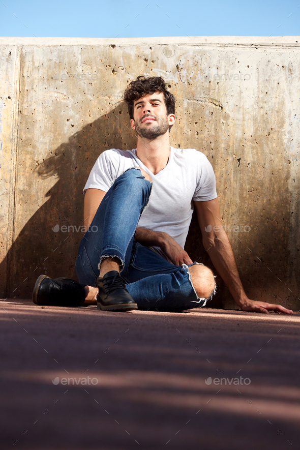 Young man sitting by concrete wall with eyes closed - Stock Photo - Images