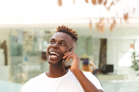 Close up laughing african young man talking on mobile phone and looking away - Stock Photo - Images