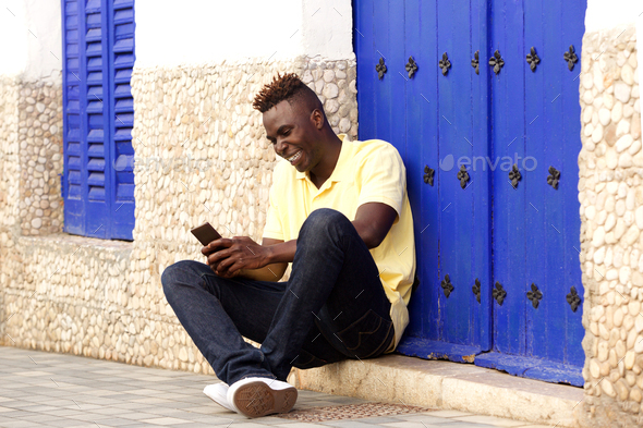 Stylish young african man sitting outside and using mobile phone - Stock Photo - Images