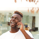 Close up laughing african young man talking on mobile phone and looking away - PhotoDune Item for Sale