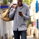 Young african american male traveler walking outside and using mobile phone - PhotoDune Item for Sale