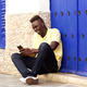 Stylish young african man sitting outside and using mobile phone - PhotoDune Item for Sale