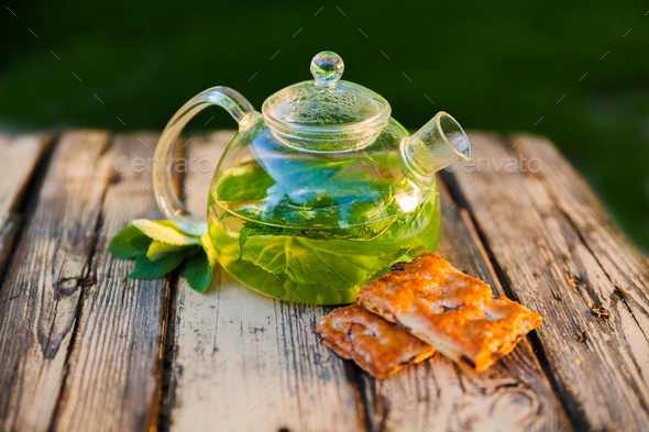 Tea pot of herbal tea on a wooden table - Stock Photo - Images