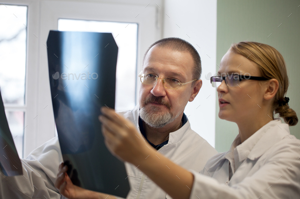 Senior and young doctors examining x-ray images - Stock Photo - Images