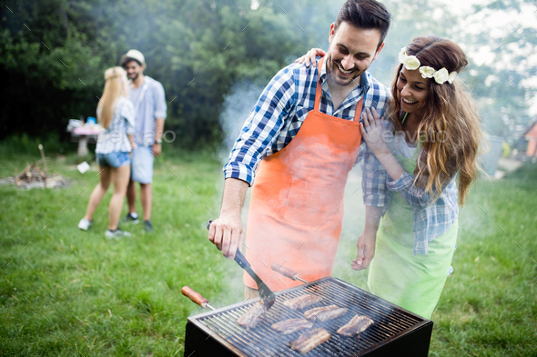 Group of happy friends having barbecue party in forest - Stock Photo - Images