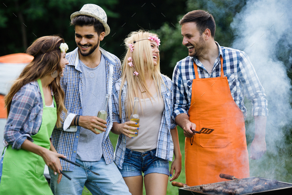 Group of happy friends having outdoor barbecue laughing together - Stock Photo - Images