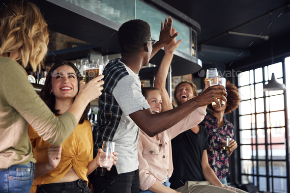 Group Of Male And Female Friends Celebrating Whilst Watching Game On Screen In Sports Bar - Stock Photo - Images