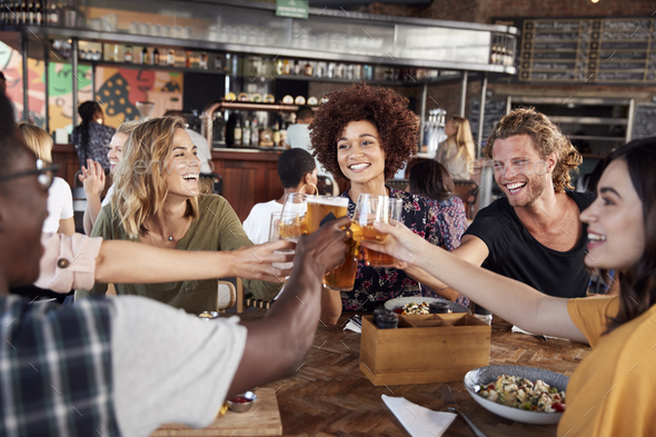 Group Of Young Friends Meeting For Drinks And Food Making A Toast In Restaurant - Stock Photo - Images