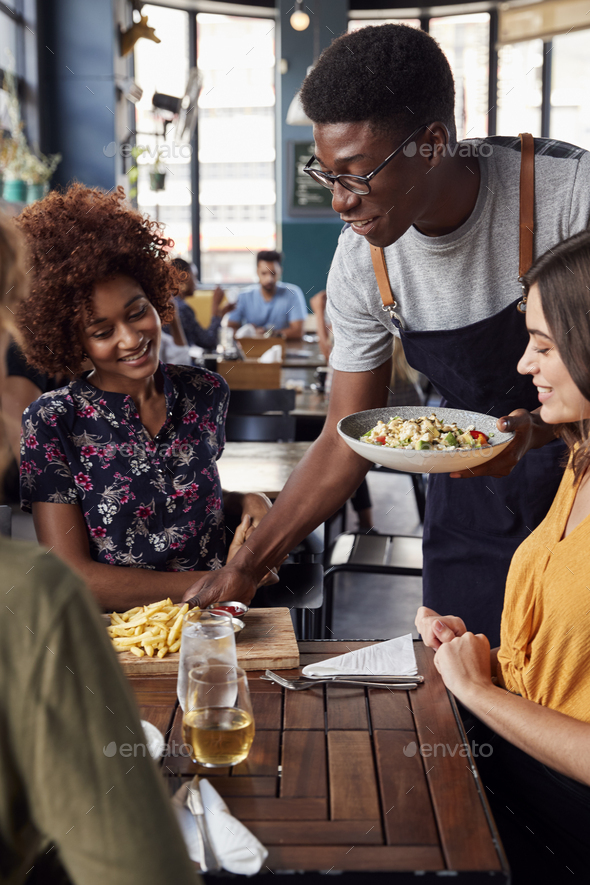 Waiter Serving Group Of Female Friends Meeting For Drinks And Food In Restaurant - Stock Photo - Images