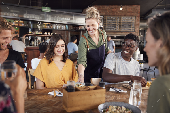 Waitress Serving Group Of Young Friends Meeting For Drinks And Food In Restaurant - Stock Photo - Images