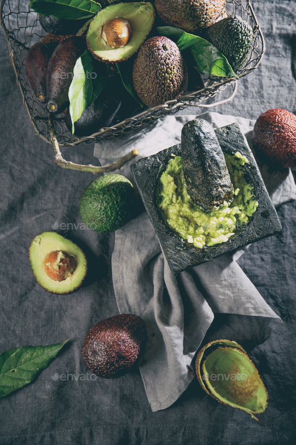 Mexican Guacamole Sauce in Stone Mortar, Full Basket with Avocado on Linen Tablecloth - Stock Photo - Images