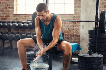 Man rubbing hand with chalk powder at gym