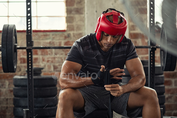 Boxer man wrapping his hands with gloves