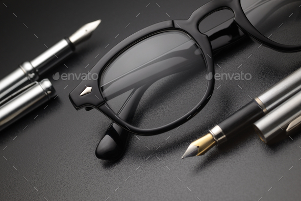 Black plastic eye glasses with two fountain pens on dark background - Stock Photo - Images