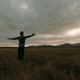 Young man standing in meadow under thunder sky - PhotoDune Item for Sale