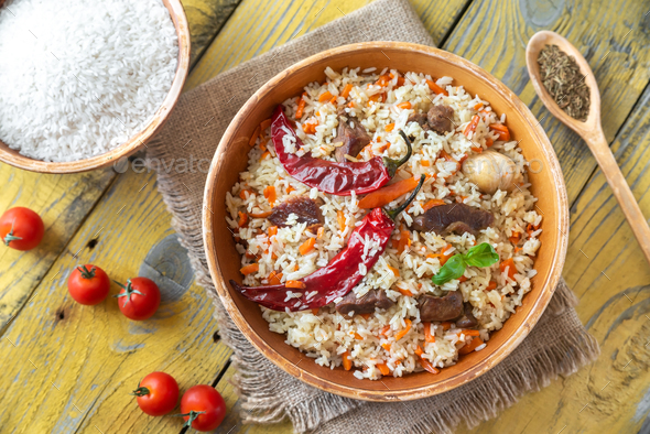Bowl of pilaf on the wooden table - Stock Photo - Images