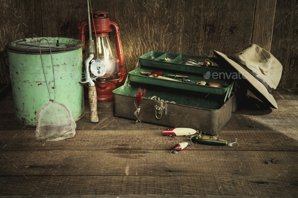 Vintage Fishing Rod And Gear With Lantern On Old Wood Backgroun