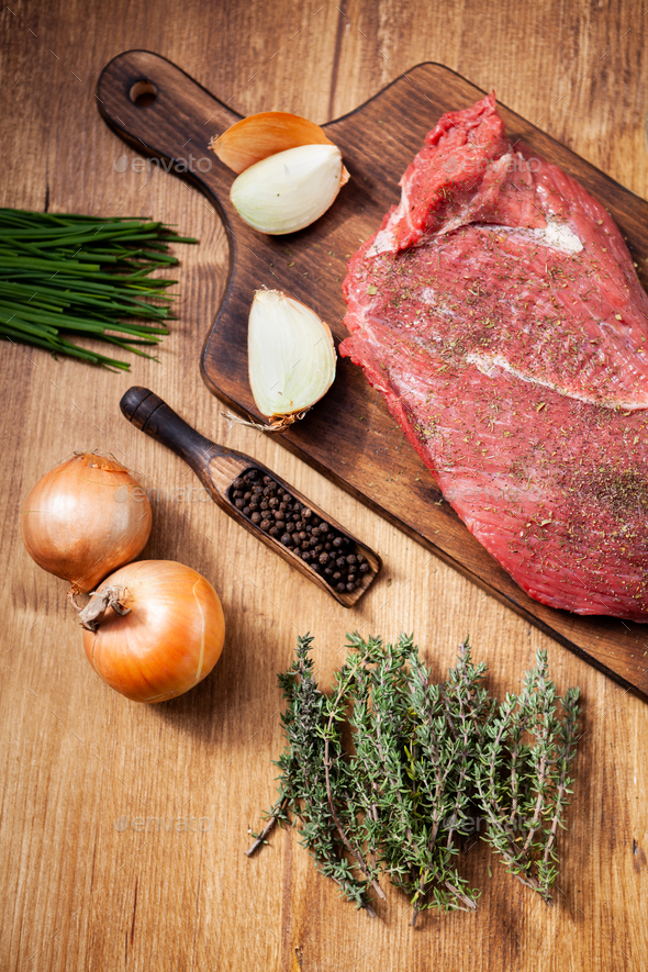 Raw meat from the butcher shop on wooden board with ingredients - Stock Photo - Images