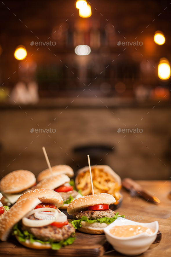 Close up of burgers with lettuce and counter bar blurred in the background - Stock Photo - Images