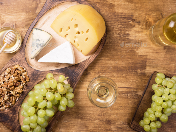 Flat lay top view of various cheeses next to fresh grapes, glass of wine on a wooden table - Stock Photo - Images