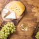 Flat lay top view of various cheeses next to fresh grapes, glass of wine on a wooden table - PhotoDune Item for Sale
