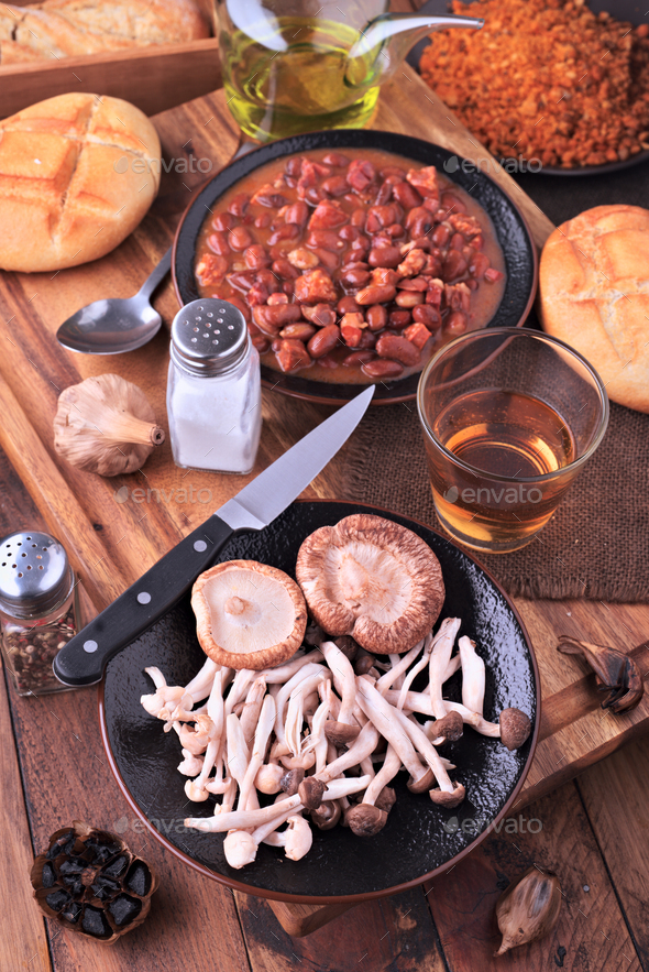 Edible mushrooms and red beans cooked on classic wooden board - Stock Photo - Images