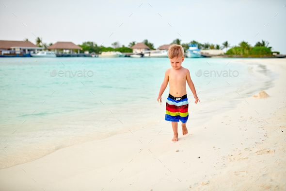 Three year old toddler boy on beach at sunset - Stock Photo - Images