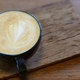 Latte coffee decorated with top leaves placed on wooden floor. - PhotoDune Item for Sale