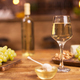 Close up of a glass of wine next to a bowl of tasty golden honey on a wooden table in a vintage pub - PhotoDune Item for Sale