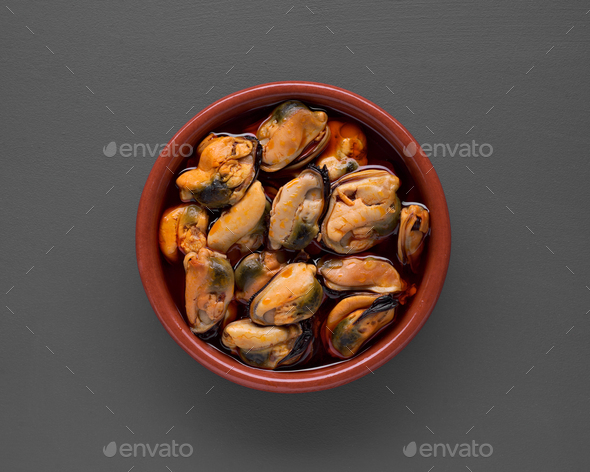 Clay pot filled with mussels in sauce isolated on gray background - Stock Photo - Images