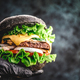 Hands in black gloves hold a big black burger with marble beef patty, cheese and fresh vegetables - PhotoDune Item for Sale