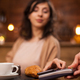 Photo of attractive woman paying with mobile phone using wireless payment on a coffee shop - PhotoDune Item for Sale