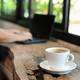 White coffee mug on the wood counter with people using the laptop on the back. - PhotoDune Item for Sale