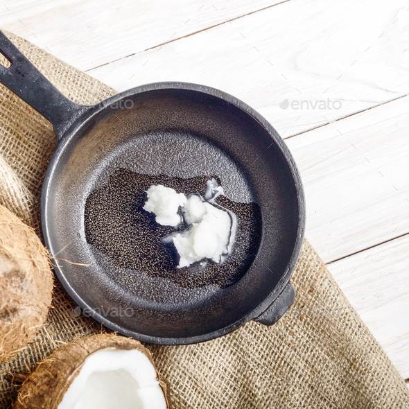 Coconut, shell with meat, cast iron skillet on hemp sackcloth on - Stock Photo - Images
