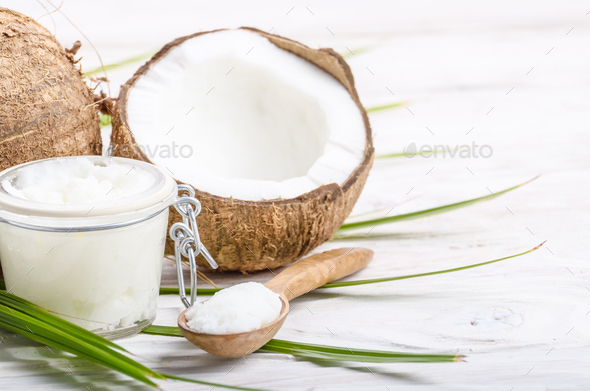 Coconut oil in airtight glass jar spoon and shell pieces on whit - Stock Photo - Images