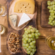 Top view of food compositon of fresh grapes next to various cheeses - PhotoDune Item for Sale