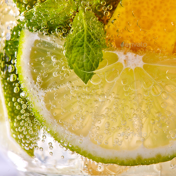Macro photo of fresh slices of green lime, yellow lemon and mint leaf with bubbles in a glass - Stock Photo - Images
