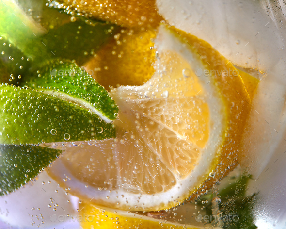 Macro photo of fresh lime and lemon slices with bubbles in the glass. Summer cold drink - Stock Photo - Images