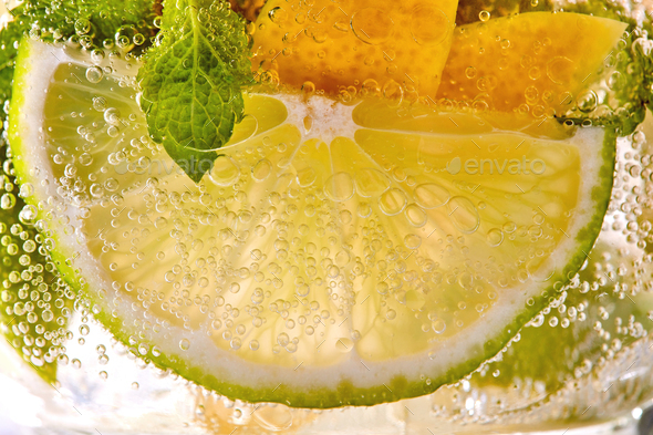 Macro photo of a summer mojito cocktail with slices of lime, lemon and mint leaves in a glass - Stock Photo - Images