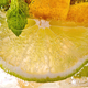 Macro photo of a summer mojito cocktail with slices of lime, lemon and mint leaves in a glass - PhotoDune Item for Sale