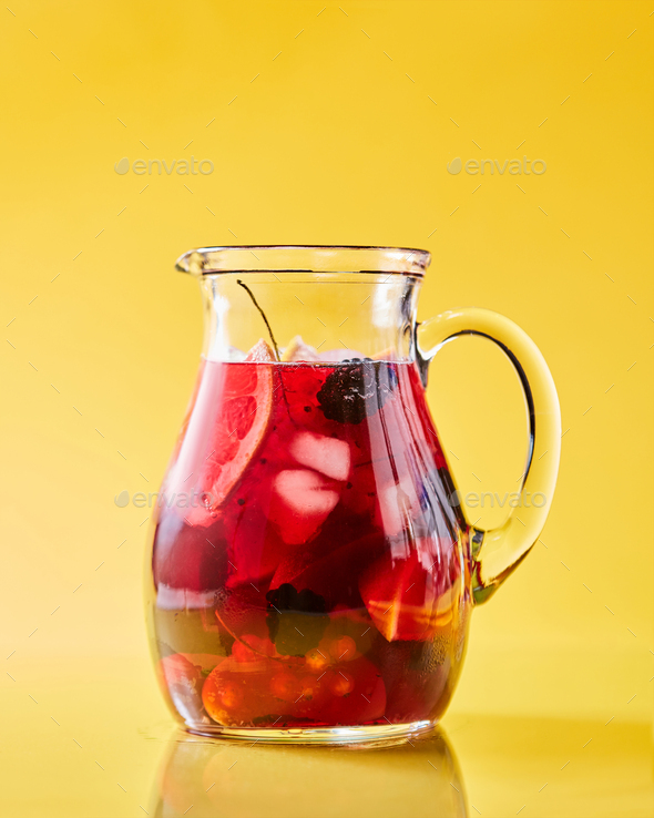 Fruit berry homemade lemonade in a glass jug on a yellow background with copy space. Healthy drink - Stock Photo - Images
