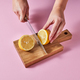 Woman's hands cut a lemon on a wooden board with a knife around a pink background with copy - PhotoDune Item for Sale