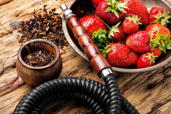 Smoking hookah on strawberry - Stock Photo - Images