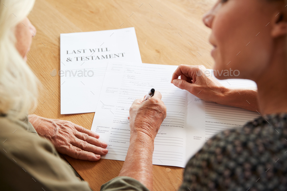 Female Friend Helping Senior Woman To Complete Last Will And Testament At Home - Stock Photo - Images