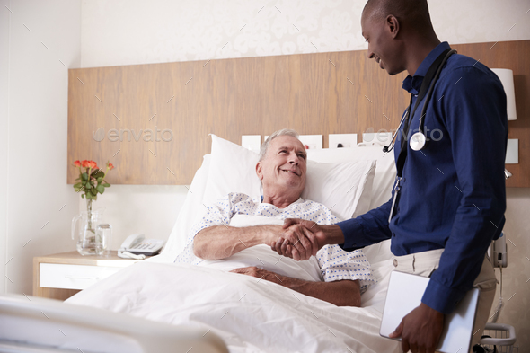 Doctor Shaking Hands With Senior Male Patient In Hospital Bed In Geriatric Unit - Stock Photo - Images