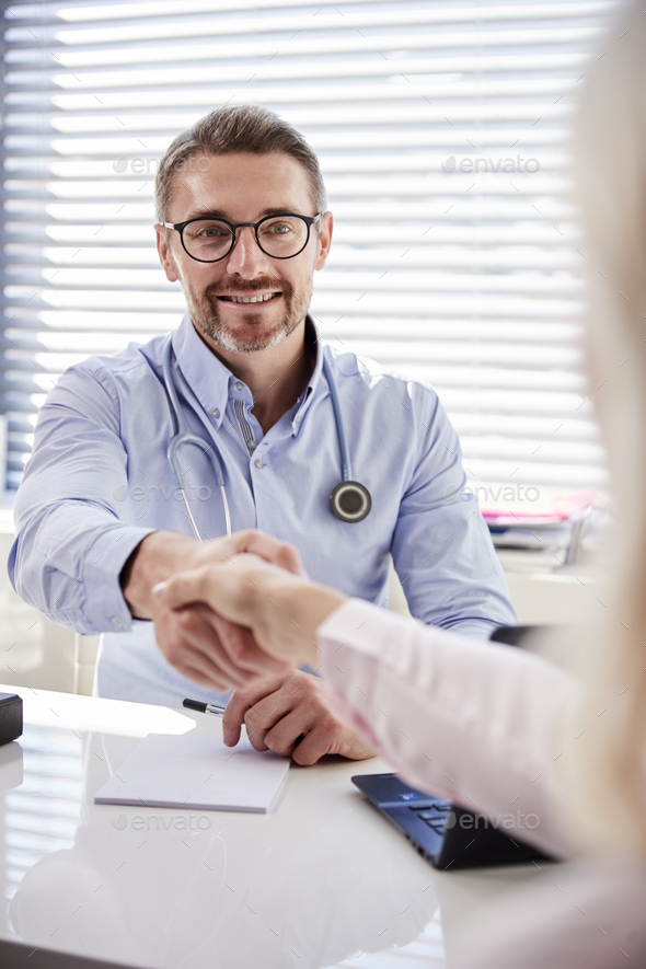 Female Patient Shaking Hands With Doctor Sitting At Desk In Office - Stock Photo - Images