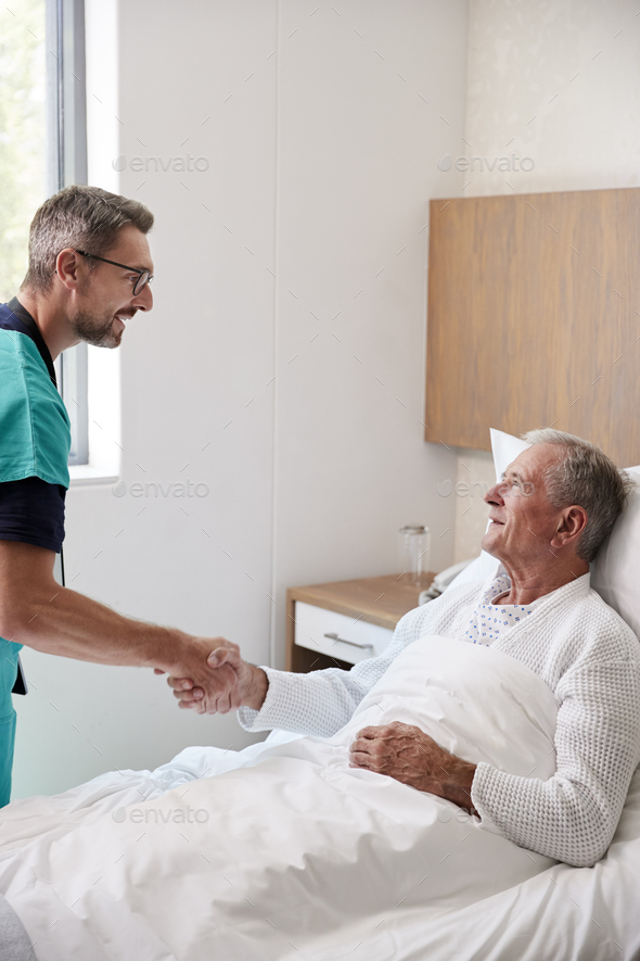 Surgeon Visiting And Shaking Hands With Senior Male Patient In Hospital Bed In Geriatric Unit - Stock Photo - Images