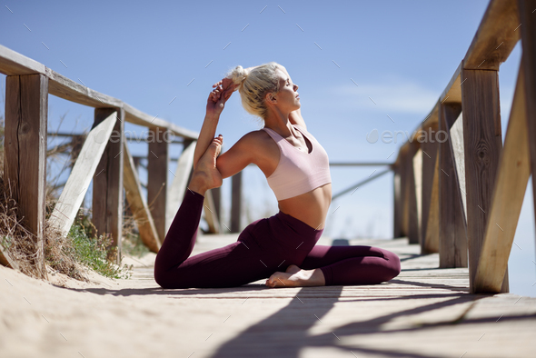 Caucasian blonde woman practicing yoga in the beach - Stock Photo - Images