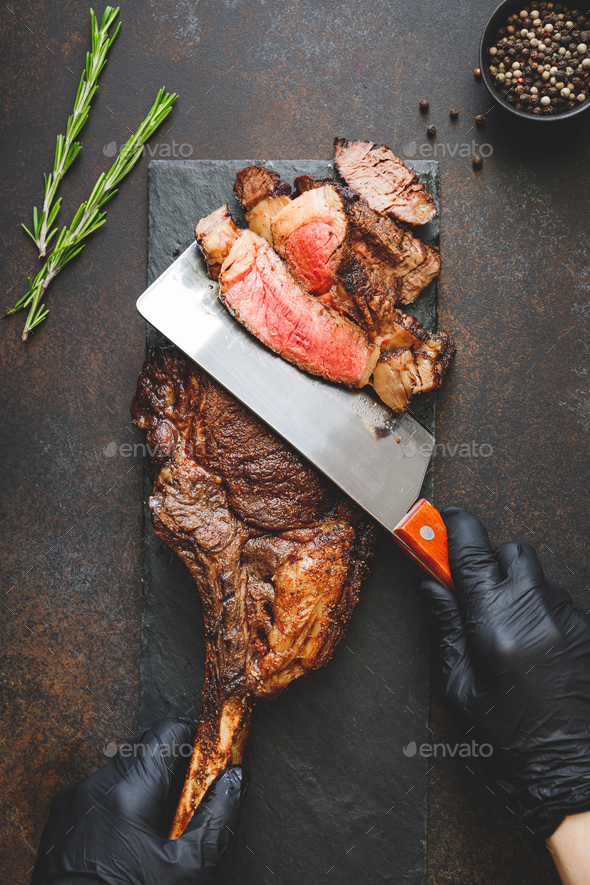 Man in black gloves cuts dry-aged marble beef steak Tomahawk. Top view, dinner concept. - Stock Photo - Images